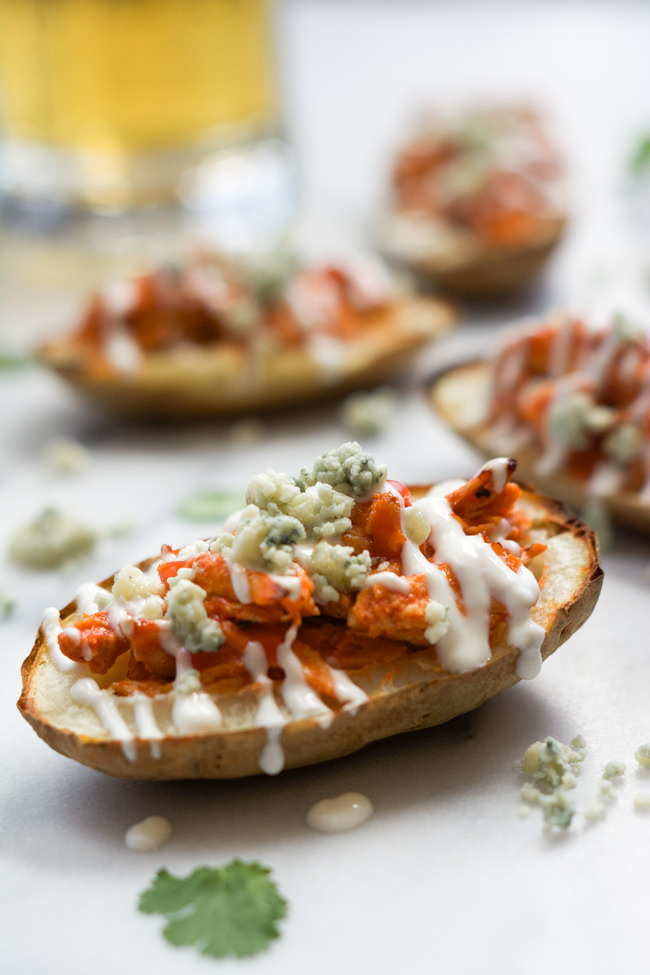 Buffalo Chicken Stuffed Potato Skins with Honey Blue Cheese Sauce are the perfect party food! Spicy shredded chicken loaded onto a crispy potato skin and drizzled with a homemade blue cheese sauce! #potatoskins #buffalo #appetizer #glutenfree